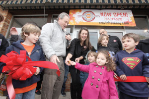 Fair Haven Mayor Ben Lucarelli cuts the ribbon at Cravin Haven with a little help from, Isabella  Mazzucca, in pink coat, and her mom, Suzanne Mazzucca, to officially open the new eatery in Fair Haven. Also helping are Andrew Cavise, Jaden  Cavise, Jack Costello, and Jack Gyimesi. By Scott Longfield