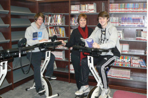 Red Bank Regional High School High School students, Ryan Grant of Shrewsbury, left, and Jacob Curtis of Little Silver, right, do some school work and exercise at the same time on RBR's new bike desks as RBR Media Specialist Kathy Smith looks on.