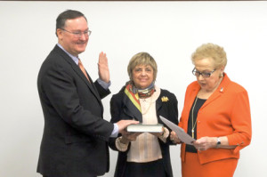 Peter T. Doyle, the newest member of the Monmouth County Library Commission, is sworn in by Freeholder Director Lillian Burry as library commission Chairwoman Renee Schwartz holds the Bible.