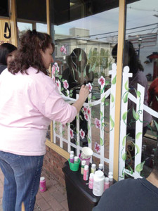 Jeanne Fary, a breast cancer survivor, helps paint a mural on the window of her sister's Atlantic Highlands salon last year as part of the Paint the Town Pink breast cancer awareness and mammography initiative.