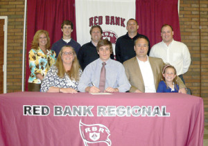 Red Bank Regional High School senior Jake Smolokoff signs to play lacrosse for NJIT's inaugural team. Attending the signing are, from left, seated: Jake's mother Maureen, Jake, his father Ron and little sister, Conley; standing are: Principal Risa Clay, Jake's brother, Cole, assistant coach Ryan Howard, head coach Don Femminella and assistant coach Mark Brown. Photo Courtesy of RBR
