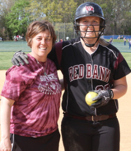 RBR softball coach Denise D'Esposito, left, and senior Jess Stevenson are all smiles after D'Esposito hands Stevenson the game ball after her 100th career hit. Photo by Scott Longfield