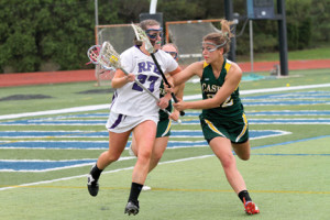 Rumson's Mary Scarone (27) turns upfield with the ball as Red Bank Catholic's Amanda Casten (22) reaches in for the check. --Photo by Sean Simmons