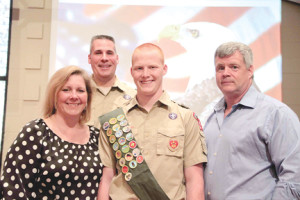 John Griffin, center, is one of only 2 percent of the 1.1 million Boy Scouts nationwide to achieve the rank of Eagle Scout. Griffin is flanked by his parents, Susan and John, at his Eagle Court of Honor with Scoutmaster Scott Pevonis in the back row. --Courtesy Troop 246