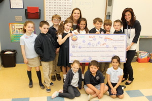Ranney School second-graders, with teacher Jennifer McDermott, center, present a copy of a check for $2,700 to Nancy Levine, right, outreach coordinator at the Juvenile Diabetes Research Foundation. The kids, headed by Salvatore Principato, standing fourth from right, created and sold more than 600 buttons to raise money for the foundation.