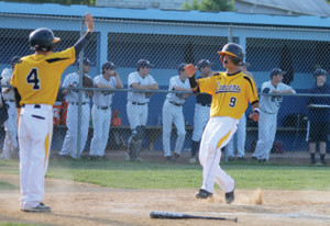 SJV's Nick Gugliara is greeted by teammate Drew Fisher as he crosses the plate and scores a run for the Lancers. The Lancers won with a score of 13-9 . --Photo by Sean Simmons