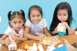 Three friends, Melissa, Irene and Juliette, enjoy a healthy lunch during a summer day session at the Boys and Girls Club in Red Bank.