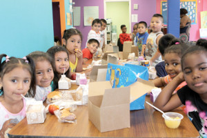 Youngsters attending a summer day program at the Red Bank Boys and Girls Club are all smiles as they eat lunch on Monday, July 14.