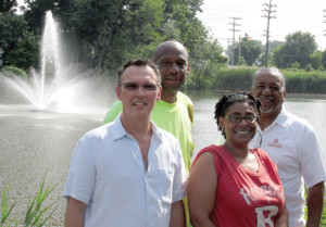 Red Bank Borough council members Edward Zipprich and Juanita Lewis, front, and Terrence Walton, back left, of the borough Department of Public Utilities and utilities Director Gary Watson show the new geyser aerator installed at Mohawk Pond at Count Basie Park on Mohawk Lane. Photo by John Burton
