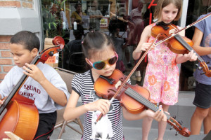 Josiah Gray, left, Lily Costa, center, and Hannah Ludwikowski of Red Bank public schools play their string instruments during a concert on Monmouth Street on Saturday, July 26, to bring attention to the loss of the strings program in the school district and efforts to raise fund to reinstate it.