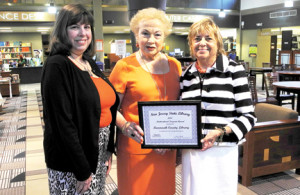 Acting Library Director Judith Tolchin, left, Freeholder Director Lillian G. Burry, center, and Monmouth County Library Commission Chair Renee B. Swartz at the Eastern Branch Library in Shrewsbury with the multicultural award given to the Monmouth County Library by the New Jersey State Library for its participation in The Big Read. --Courtesy Monmouth County Library