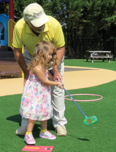 "Ava Jordan ""AJ"" Kassinger gets some pointers on her putting from Joe Ginger, a retired Professional Golfers Association pro, during lessons at The Goddard School in Tinton Falls. Photo by Michele J. Kuhn"