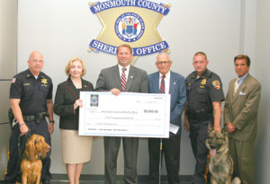 Members of the 200 Club of Monmouth County present a check to the Monmouth County Sheriff's Office for its K-9 donation fund. They are, from left: Sheriff's Officer Kurt Kroeper with K-9 Skye; M. Claire French, president of the 200 Club; Sheriff Shaun Golden; William Wingard, secretary of the 200 Club; Sheriff's Officer Michael Mindo with K-9 Tango; and Undersheriff Michael Donovan.