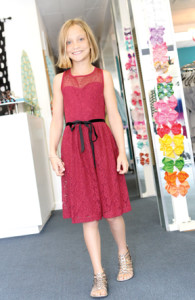 Caroline Durkin, 10, tries on the burgundy Catherine Lace Dress by Blush By Us Angels at Moon Child in Fair Haven.