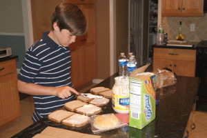 Cameron Acken give his mom a hand by preparing sandwiches for lunch. Photo courtesy Regina Acken