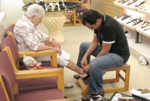 Moses Fahmy, right, helps customer Barbara Goldstein purchase the last pair of shoes she will buy from Red Bank's If The Shoe Fits, which is closing Tuesday, Aug. 26. The18 Broad St. shop has been home to a number of shoe stores since 1883. Photo by John Burton