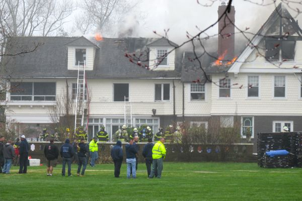 Firefighters douse flames on the roof and near the chimney of a historic home on Buena Vista Avenue in Rumson, called Blithewald, on April 20, 2015. Photo by John Burton