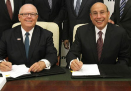 At left, Stephen K. Jones, President and CEO of Robert Wood Johnson University Hospital and Robert Wood Johnson Health System, and Barry H. Ostrowsky, President and CEO of Barnabas Health, sign the definitive agreement outlining the merger between Robert Wood Johnson Health System and Barnabas Health.
