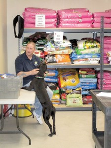Ken McKeel, manager of the Monmouth County SPCA's Pet Pantry, with Lucky, a 1-year-old, male pit bull mix. Photo: Joseph Sapia