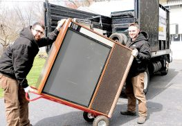 Dane DeBartolo, left, and John Doherty, of Jersey Junkers remove an old, large screen television during a recent house clean-up in Middletown.