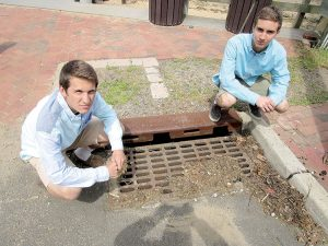 Tyler Lubin, left, and Noah Tucker at a storm drain at the Navesink River in Fair Haven. The debris buildup on at the drain shows what can flow into the river.