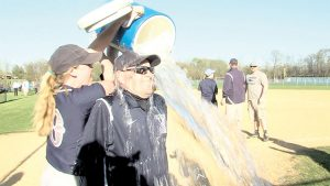 Tom Erbig gets doused with water to celebrate his 722nd win as Middletown South softball coach. Photo: Rich Chrampanis