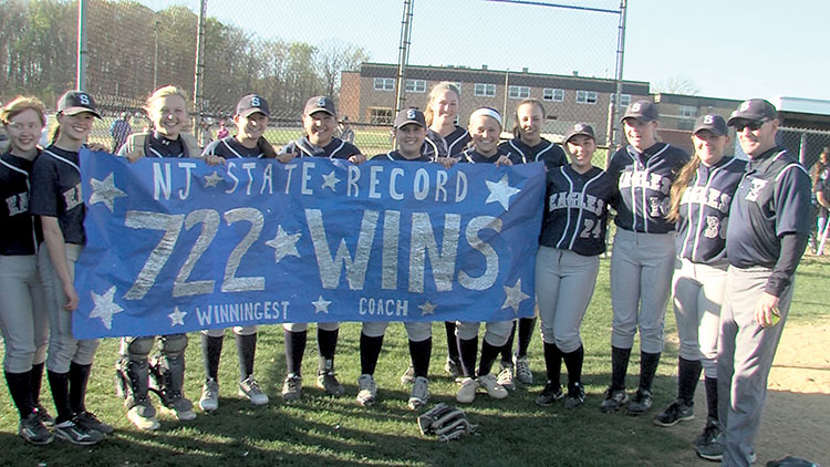 The Middletown South softball team poses with a banner commemorating Tom Erbium's record setting win. Photo: Rich Chrampanis