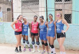 :  Catherine Curtin (far left) and Ava Zockoll (far right) pose with new friends made on their recent trip to Cuba. The two girls designed the red and blue shirts as gifts for the volleyball players, who typically wear street clothes to play. The two choices allowed the players to have competing team colors.