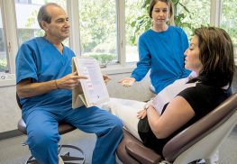 Robert M. Sacks, D.D.S., left, and his assistant Alycia Jeronimus, explain the dental implant procedure to Christine Hirsch, a patient. --Photo by Anthony V. Cosentino