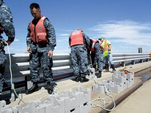 Workers ready oyster castles on the pier at Naval Weapons Station Earle. The castles were lowered into the shallow Raritan Bay waters, creating an artificial reef.