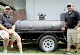 Jeff Johnson, campus minister at St. John Vianney, Holmdel, left, and his brother Mark transformed a hobby into a summer business when they started Boss Hog Barbecue four years ago.