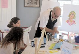 Wesley Fox, right, a resident of United Methodist Communities at The Wesleyan in Red Bank, offers some instruction in art for those attending the Wesleyan Café senior program.