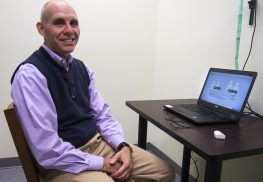 Andrew S. Burstiner, M.D., sits beside the QbTest in his Tinton Falls office. This test, which is FDA-approved, will soon be the key tool in both diagnosing and treating ADHD. --Photo by Anthony V. Cosentino