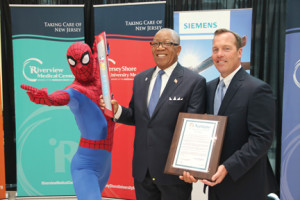 "Spider-Man ""Passes the Baton"" to Neptune Mayor Michael Brantley, center, and Tim Hogan, regional hospital president, Monmouth County, Meridian Health, in celebration of innovative cancer research. -Courtesy Meridian Health"