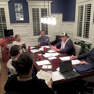 Members of the Shore to Help Board of Trustees discuss upcoming plans. Center: Mark Gardner, vice president of Shore to Help, and Ken Shaw (wearing hat), president. Photo courtesy Shore to Help