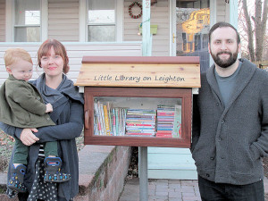 Kate Triggiano, holding her son, Otto, and her husband, David, have started a Little Free Library in front of their Red Bank home, making books available for neighborhood children. Photo: John Burton
