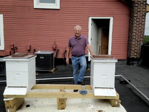 Tim Shaheen of Builders' General Supply Company with his hives on the building's rooftop.