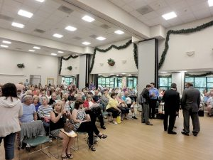 A packed house at the James J. Cullen Recreation Center in Hazlet on June 28. To the right, Assemblywoman Amy Handlin speaks with local elected officials.